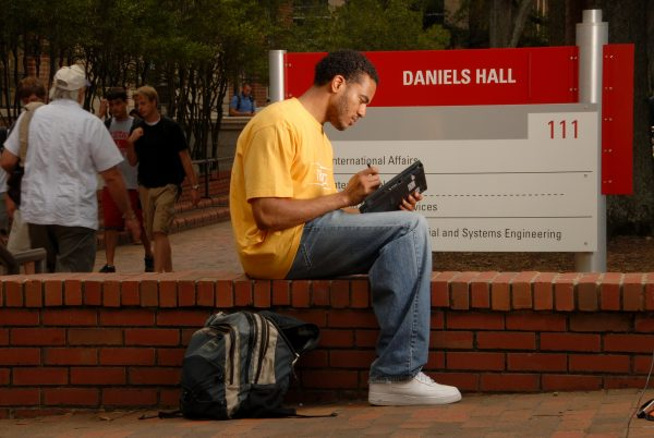 Before heading inside for class, an ISE student works on his computer in front of Daniels Hall.